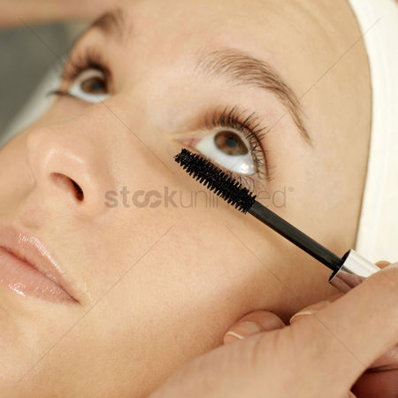 Careful : Hand curling up woman s eyelash with a mascara wand