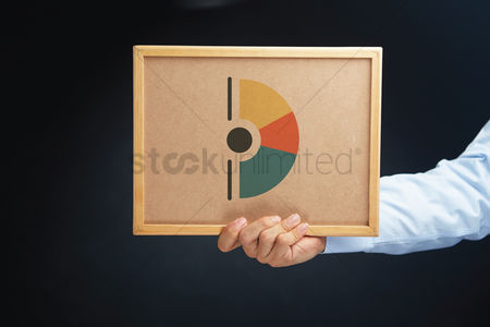 Cork board : Hand holding a board with ring charts