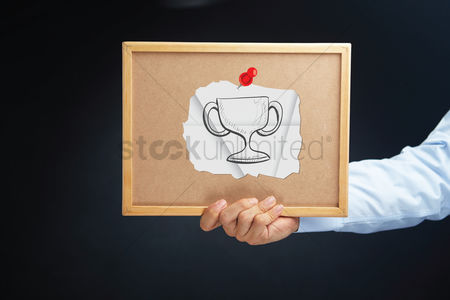 Cork board : Hand holding a board with trophy concept