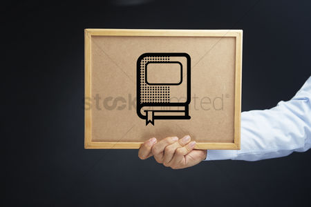 Cork board : Hand holding a cork board with a book