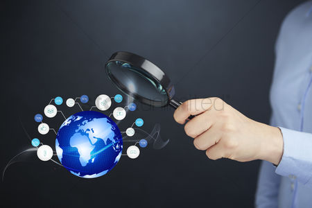 Magnifying glass : Hand holding a magnifying glass with globe and internet icons