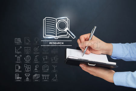 Magnifying glass : Hand holding a pen and book with research concept