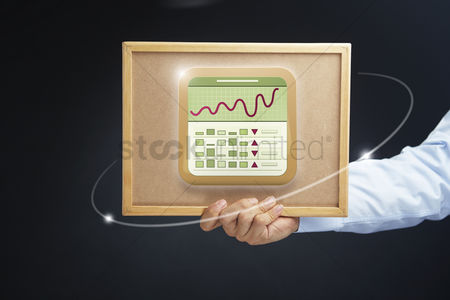 Applications : Hand holding board with stock market icon