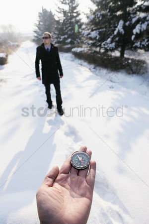Cold temperature : Hand holding compass  businessman walking in the background