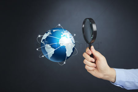 Magnifying glass : Hand holding magnifying glass with globe concept