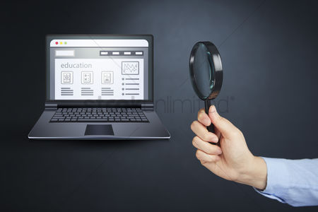 Magnifying glass : Hand holding magnifying glass with laptop and education concept