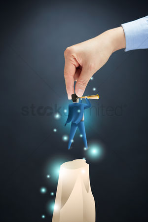 Grasp : Hand placing businessman on a cliff