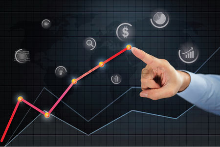 Magnifying glass : Hand pointing towards business finance point on line chart concept
