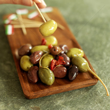 Tasty : Hand taking fresh italian olive with italian flag pick from wooden plate