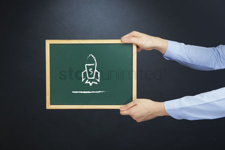 Handdrawn : Hands holding chalkboard with rocket launch drawing
