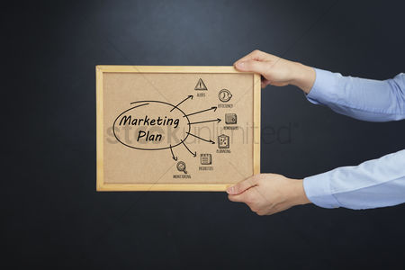 Cork board : Hands holding cork board with marketing plan concept