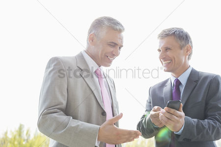 40 44 years : Happy businessmen discussing over mobile phone outdoors