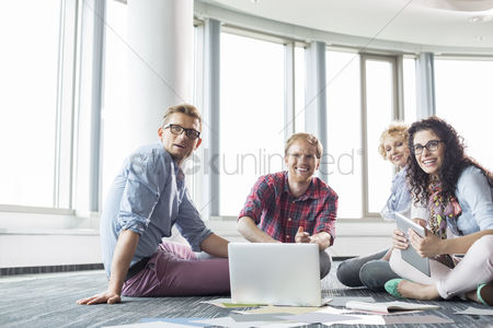 Three quarter length : Happy businesspeople looking away while working on floor at creative office