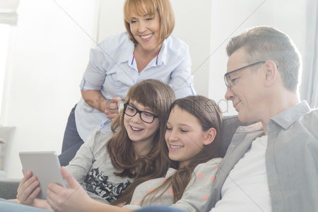 Internet : Happy family using tablet pc on sofa at home
