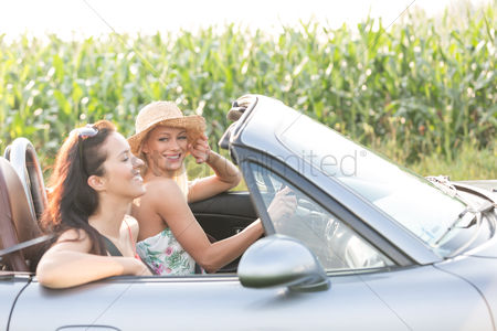 On the road : Happy female friends enjoying road trip in convertible