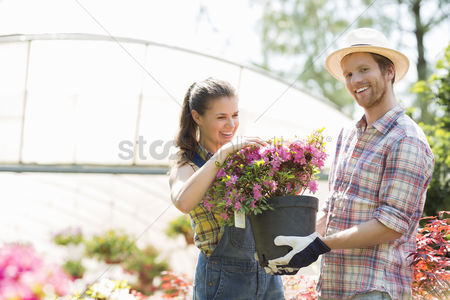 Greenhouse : Happy gardeners holding flower pot outside greenhouse