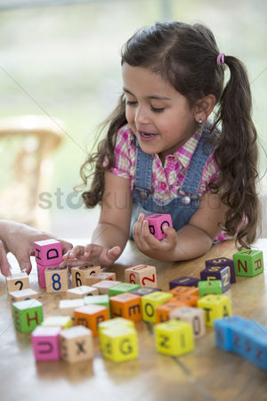 Czech republic : Happy girl playing with alphabet blocks at table