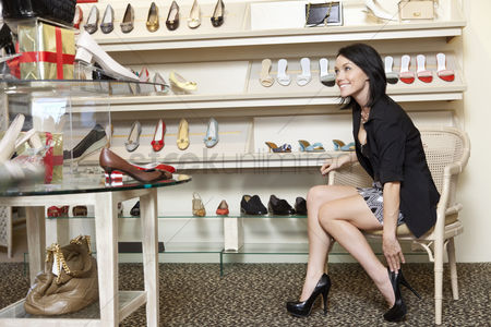 Fashion : Happy mid adult woman trying high heels in footwear store