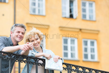 On the road : Happy middle-aged couple with map leaning on railing against building