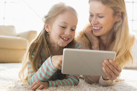 Daughter : Happy mother and daughter using digital tablet on floor at home