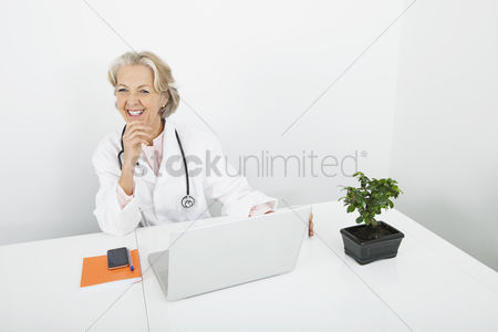 Senior women : Happy senior female doctor with laptop at desk in clinic