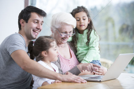 Young woman : Happy three generation family using laptop at table in house