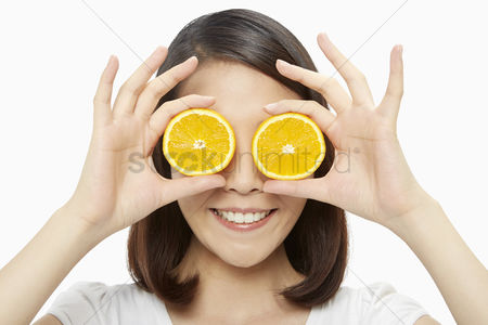 Vision : Happy woman covering both her eyes with an orange