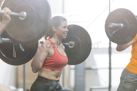 Three quarter length : Happy woman lifting barbell in crossfit gym