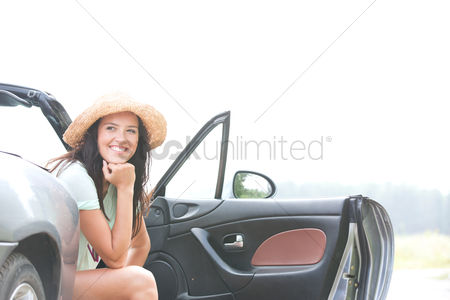 On the road : Happy woman sitting in convertible against clear sky