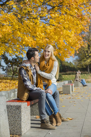 Sitting on lap : Happy woman sitting on man s lap at park during autumn