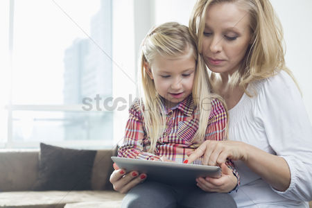 Sitting on lap : Happy woman with daughter using digital tablet in living room
