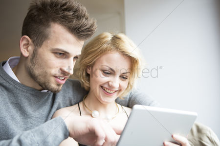 Czech republic : Happy young couple using digital tablet in cafe