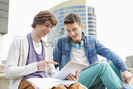 College : Happy young male college students using digital tablet against building
