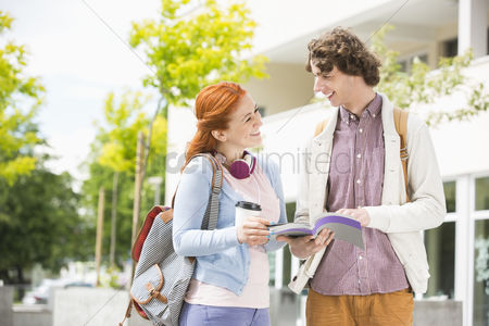 College : Happy young man and woman studying together at college campus