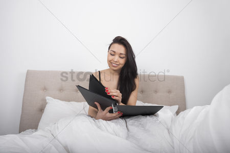 Notepad : Happy young woman with spiral notepad in bedroom