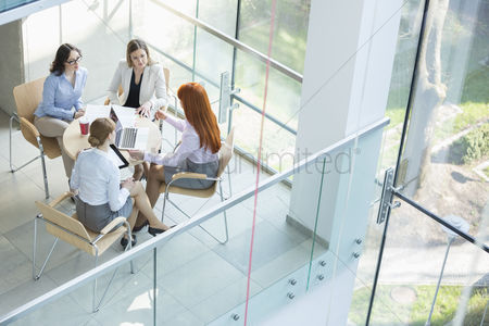 Three quarter length : High angle view of businesswomen discussing at table in office