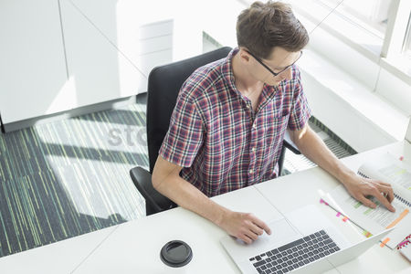 Internet : High angle view of creative businessman working at desk in office