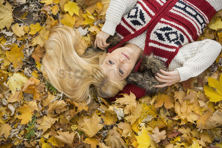 Jacket : High angle view of thoughtful young woman lying on autumn leaves in park