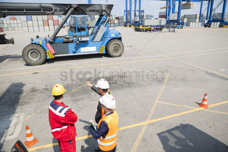 Forklift : High angle view of workers discussing in shipping yard