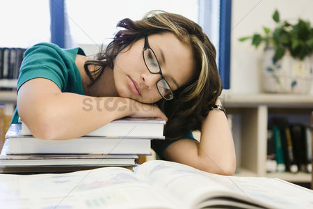 High school : High school student sleeping on a stack of books
