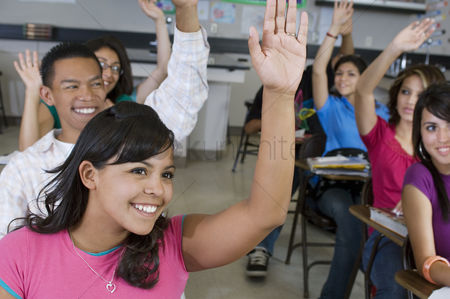 Young boy : High school students raising their hands in class