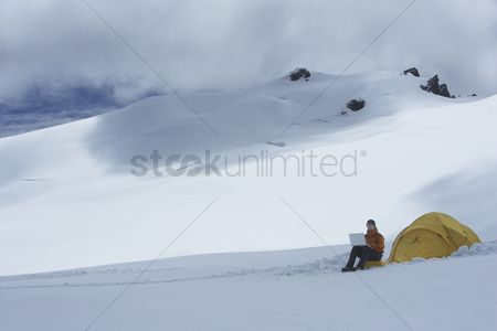 Sitting on lap : Hiker using laptop outside of tent on snowy mountain peak