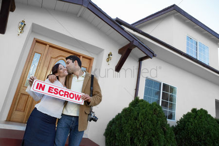 Kissing : Homeowners standing in front of house portrait