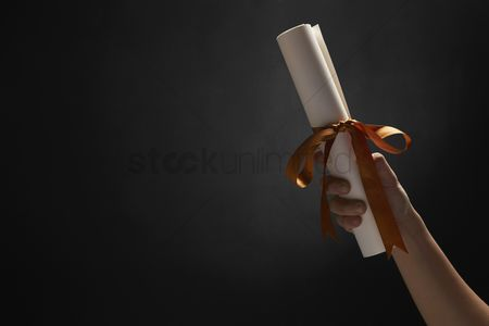 Individuality : Human hand holding a graduation scroll