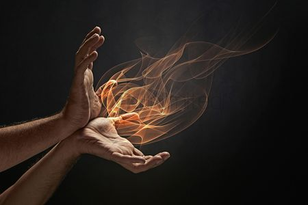 Black background : Human hands with fire coming out of it