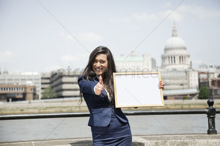 England : Indian businesswoman gesturing thumbs up as she holds moodboard sign with st  paul s cathedral in background