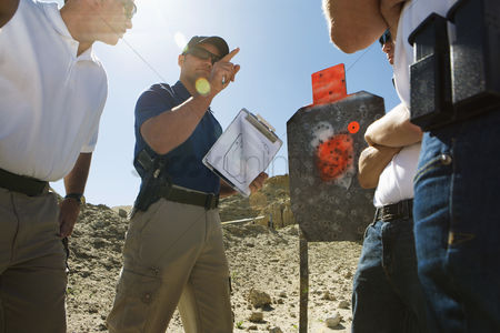 Firing : Instructor holding clipboard with target diagram at combat training