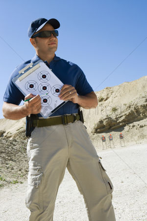 Firing : Instructor holding clipboard with target diagram at firing range