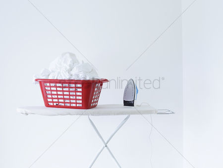 Interior : Iron and laundry basket on ironing board against white wall