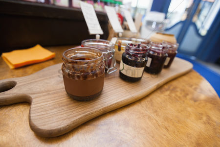 Supermarket : Jars of preserves on cutting board in grocery store